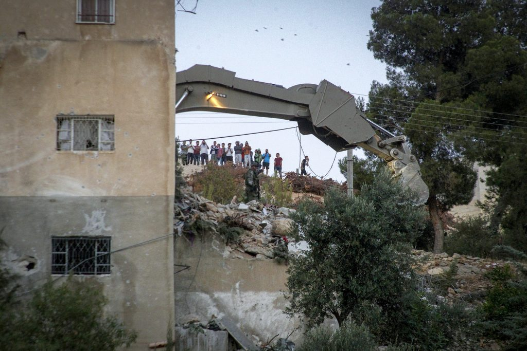 An Israeli excavator demolishes a house where Hamas fighter Mohammad al-Fakih, who murdered Rabbi Miki Mark in a terror attack a few weeks ago, was shot dead by Israeli troops during a raid in the West Bank village of Surif, near Hebron on July 27, 2016. Photo by Wisam Hashlamoun/FLASH90 *** Local Caption *** חמאס חיילים חייל