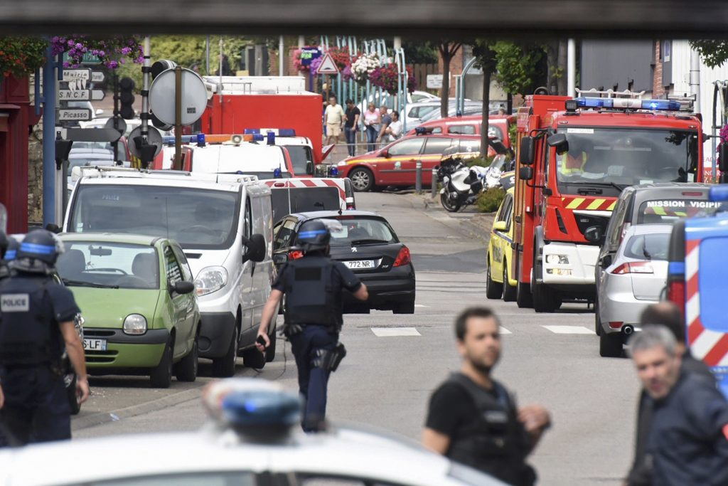 Police and rescue workers stand at the scene after two assailants had taken five people hostage in the church at Saint-Etienne-du -Rouvray near Rouen in Normandy, France, July 26, 2016. Two attackers killed a priest with a blade and seriously wounded another hostage in a church in northern France on Tuesday before being shot dead by French police. REUTERS/Steve BonetATTENTION EDITORS FRENCH LAW REQUIRES THAT VEHICLE REGISTRATION PLATES ARE MASKED IN PUBLICATIONS