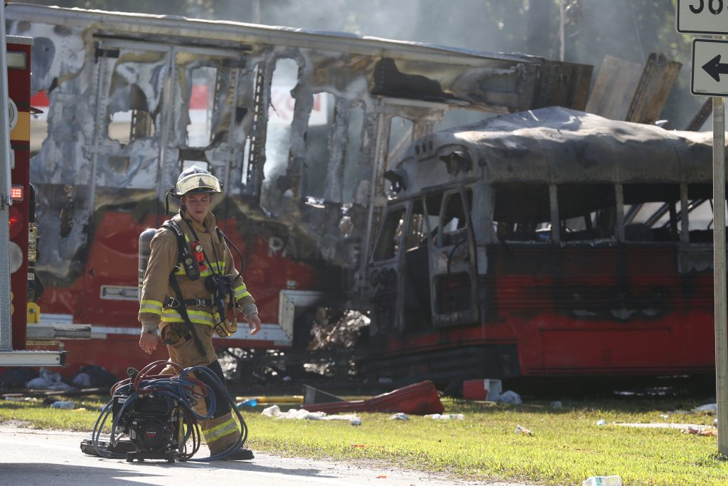 Wakulla County first responders work on the scene of an accident on Saturday, July 2, 2016 in Wakulla, Fla. The Florida Highway Patrol says a bus and tractor trailer collided on a highway in the Panhandle. Florida Highway Patrol Capt. Jeffrey Bissainthe says the bus was carrying between 30 and 35 passengers and was from Georgia. (Joe Rondone /Tallahassee Democrat via AP)