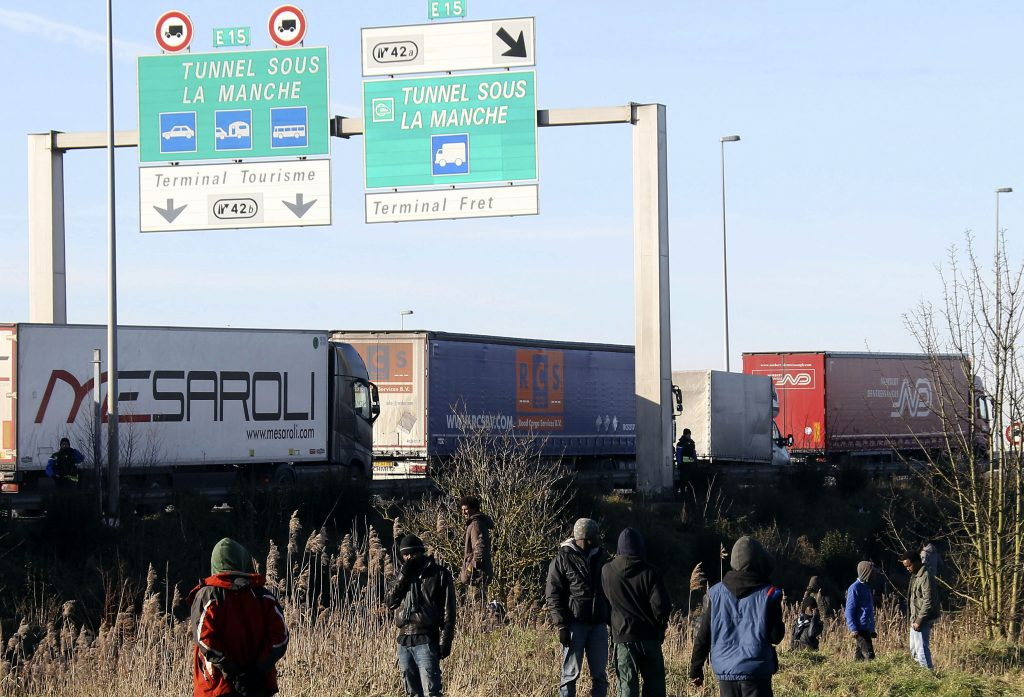 FILE - In this Jan.21, 2016 file photo, migrants attempt to board trucks lining up to enter the Channel Tunnel in Calais, northern France. Calais Mayor Natacha Bouchart shares the dream of thousands of migrants massed in her city on the English Channel _ she wants them to leave for Britain. But undoing a French-British treaty that keeps them trapped on the French side of the border is a pipe dream. (AP Photo/Michel Spingler, File)