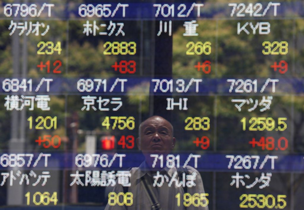 A man is reflected on a stock quotation board outside a brokerage in Tokyo, Japan July 11, 2016. REUTERS/Issei Kato