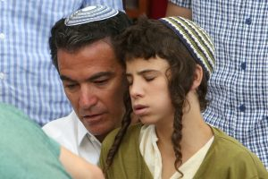 """Mossad chief Yossi Cohen (L) holds the son of Rabbi Michael Mark, Hy""""D, at the levayah on Sunday. (Menahem Kahana/AFP/Getty Images)"""