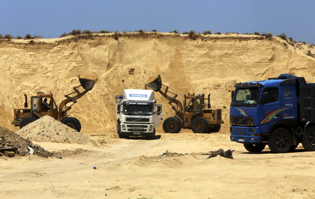 Palestinian diggers dump sand into a truck at the site of Al-Isra 2 housing project in Khan Younis, Gaza Strip, where Jewish communities thrived until 2005. Hamas has begun handing out plots of public land to 40,000 civil servants loyal to it. (AP Photo/Adel Hana)