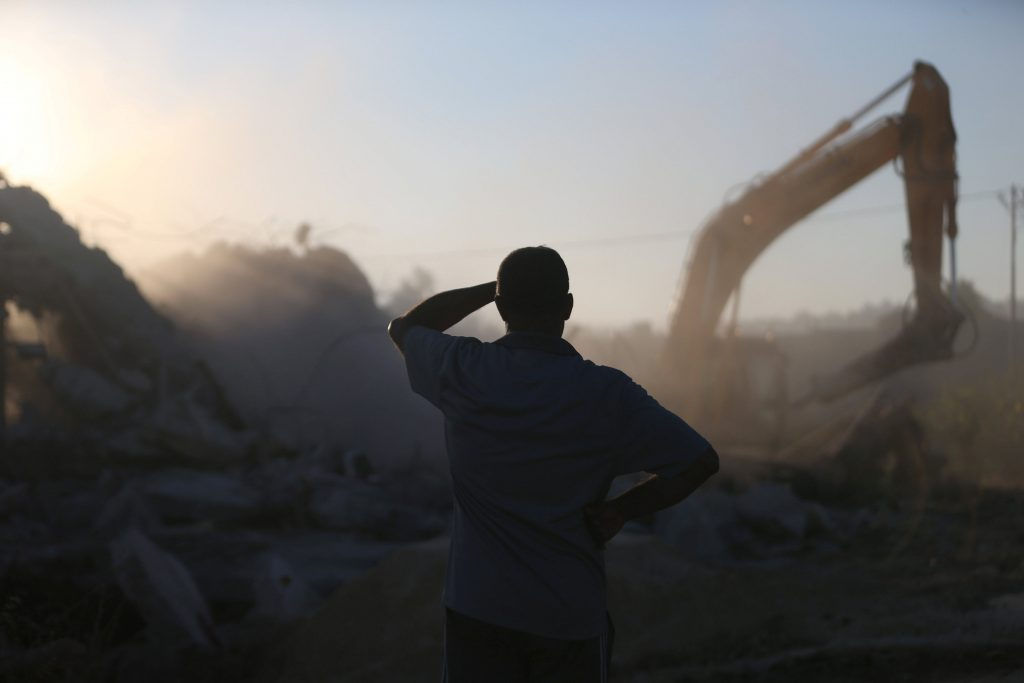 A Palestinian man looks at Israeli machinery as it demolishes a Palestinian house in the West Bank village of Qalandia near Ramallah, July 26, 2016. REUTERS/Mohamad Torokman