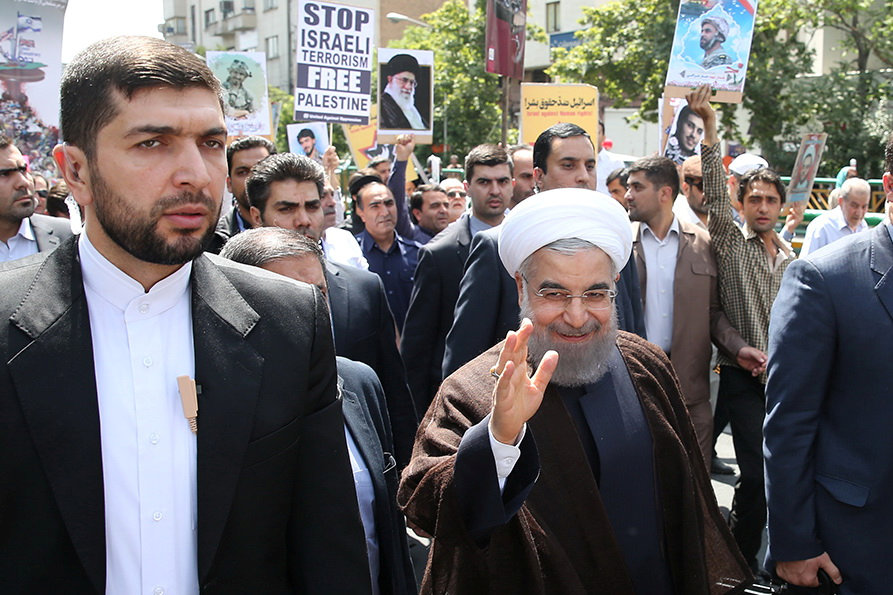 Iran's President Hassan Rouhani waves during a rally in support of the Palestinians, in Tehran, Sunday. (Handout via Reuters)