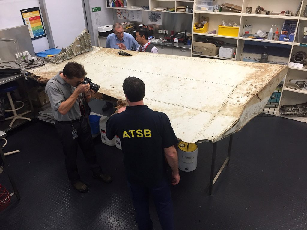 Australian and Malaysian officials examine aircraft debris at the Australian Transport Safety Bureau headquarters in Canberra, Australia, July 20, 2016 after it was found on Pemba Island, located near Tanzania, in late June and was transported to Australia for examination. Australian Transport Safety Bureau/Handout via REUTERS ATTENTION EDITORS - THIS IMAGE WAS PROVIDED BY A THIRD PARTY. EDITORIAL USE ONLY. NO RESALES. NO ARCHIVE. MANDATORY CREDIT TPX IMAGES OF THE DAY