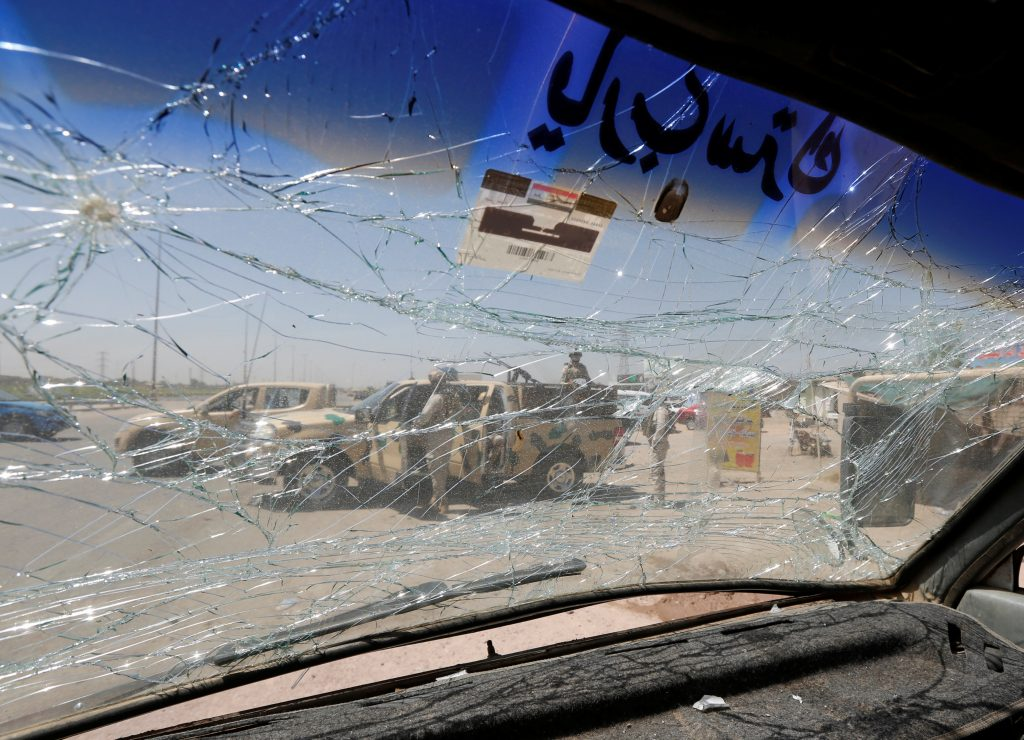 An Iraqi security vehicle is pictured through a shattered windshield of a vehicle damaged at the site of car bomb attack in Rashidiya a district north of Baghdad, Iraq July 12, 2016. REUTERS/Ahmed Saad