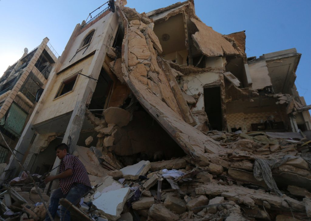 A man walks down over the rubble of a damaged building after an airstrike on Aleppo's rebel held Saif al-Dawla district, Syria July 2, 2016. REUTERS/Abdalrhman Ismail