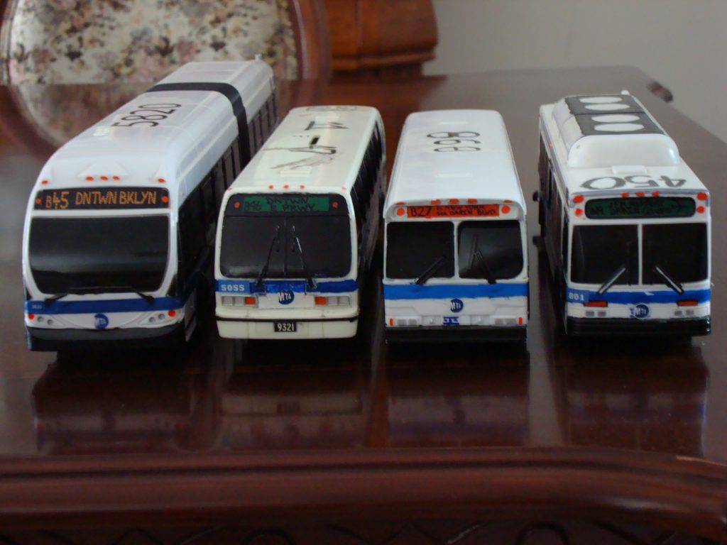 Miniature New York City buses are lined up on a table in New York. (Flickr/King Of All Buses)