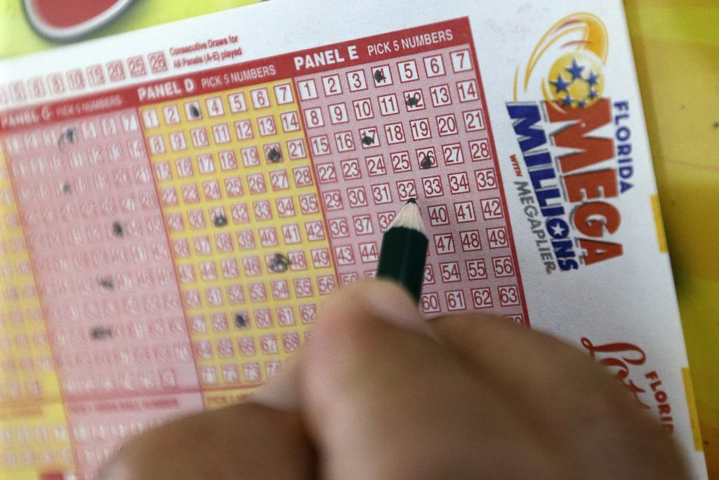 A customer fills out a Mega Millions ticket at a local grocery store, Friday, July 1, 2016, in Hialeah, Fla. Friday night's Mega Millions drawing will give lottery players a shot at the 10th largest jackpot in U.S. history. (AP Photo/Alan Diaz)