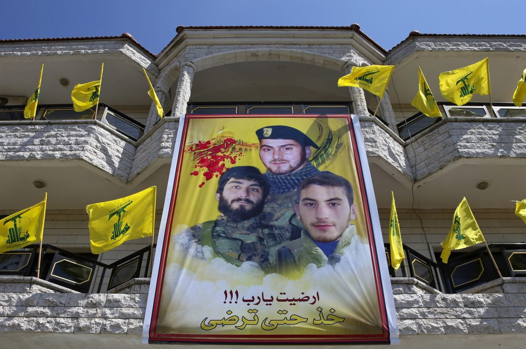 A poster showing portraits of Mahdi Daqiq, top, and his nephew Mohammed Daqiq, right, who were killed during fighting with Israel in the 2006 war; and his nephew Ali Daqiq who was killed in Khalsa, southern Aleppo, on June 16, 2016, hangs on their family house, in the southern village of Harees, Lebanon. (AP Photo/Hassan Ammar)