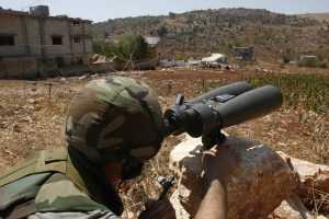 In this Aug. 16, 2006, photo, a Hizbullah terrorist, who refused to be identified, uses binoculars to scan for Israeli forces' positions, in the outskirts of the southern village of Aitaroun, close to the town of Bint Jbeil. (AP Photo / Mohammed Zaatari, File)