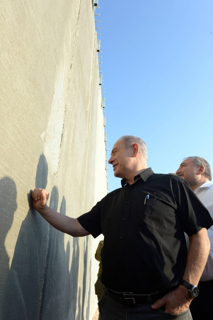 Israeli Prime Minister Binyamin Netanyahu (in black shirt), and Defense Minister Avigdoe Liberman inspecting the new security wall under construction in the South Chevron Hills on Wednesday. (Haim Zach/GPO)