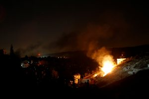 Flames are seen during a raid by Israeli forces on a house in which Palestinian Hamas fighter Mohammad al-Fakih was hiding out in the West Bank village of Surif, near Hebron July 27, 2016. REUTERS/Mussa Qawasma