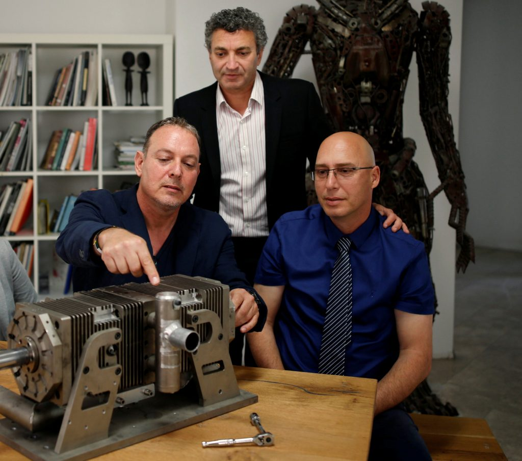 Shaul Yaakoby (R), CTO and Inventor, Gal Fridman (C), Chief Marketing Officer, Maya Gonik (L), Head of Business Development and Ariel Gorfung (standing), Chief Executive Officer from Israeli start-up Aquarius Engines pose for a picture next to a prototype of their combustion engine at their offices in Rosh Ha'ayin, Israel May 16, 2016. Picture taken May 16, 2016. REUTERS/Amir Cohen
