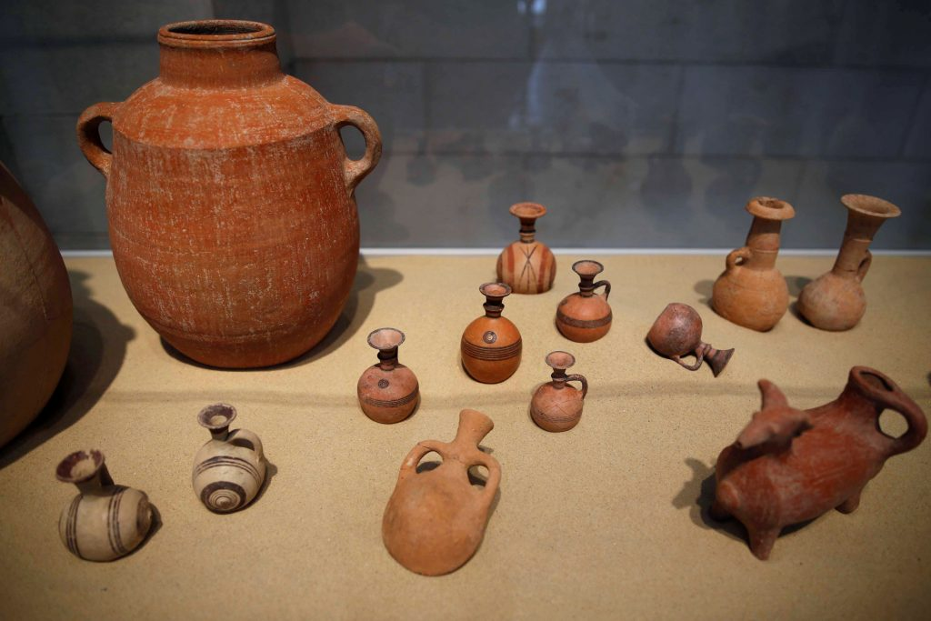 Clay items unearthed during excavations at the first-ever-discovered Philistine cemetery in Ashkelon National Park, are displayed at an exhibition in the Rockefeller Museum in Yerushalayim on Wednesday. (Reuters/Amir Cohen)
