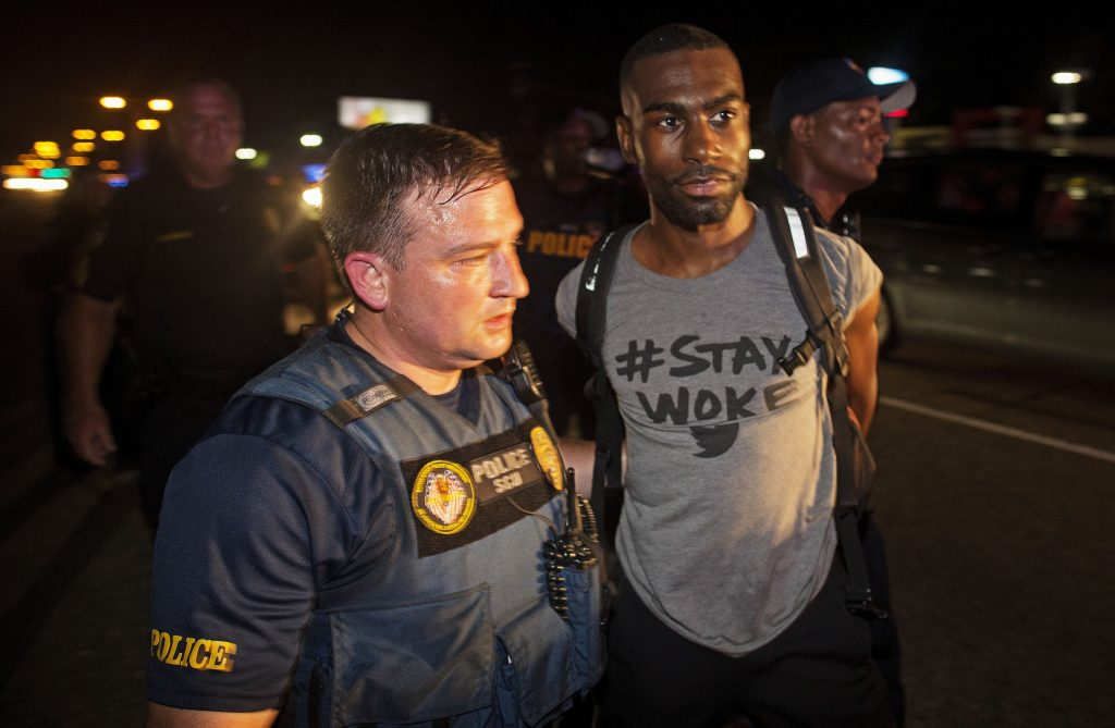 Police arrest activist DeRay McKesson during a protest along Airline Highway, a major road that passes in front of the Baton Rouge Police Department headquarters, on Saturday. (AP Photo/Max Becherer)