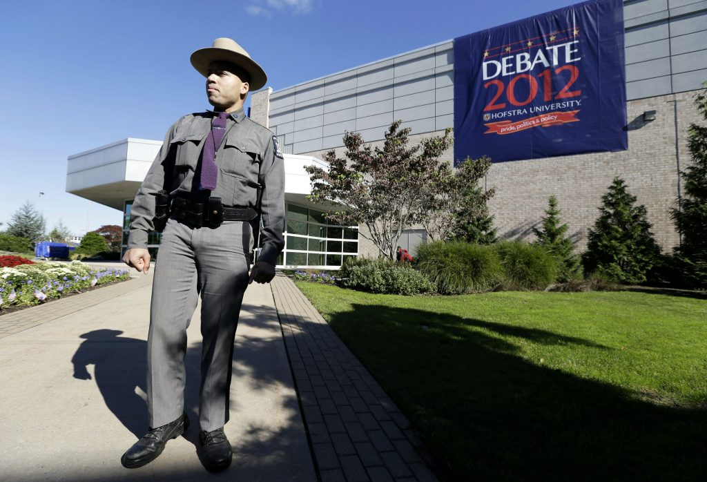 In this Oct. 16, 2012 photo, a New York state trooper Gary DePass stands outside the site of a debate between presidential candidates Barack Obama and Mitt Romney, at Hofstra University's David S. Mack Sports Complex in Hempstead, N.Y. The Commission on Presidential Debates announced Tuesday, July 19, 2016, that Hofstra University will host the 2016 general election's first presidential debate on Monday, Sept. 26. (AP Photo/Charlie Neibergall, File)