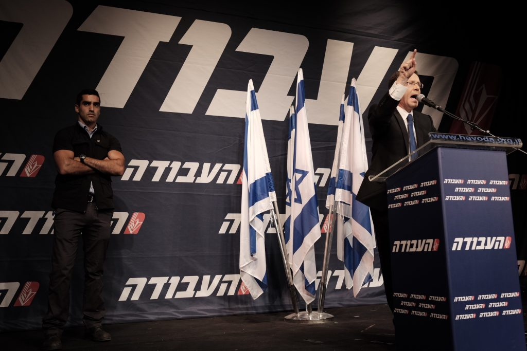 Leader of the Israeli Labor Party Isaac Herzog confronts rowdy internal opposition at a party convention on Sunday. (Tomer Neuberg/Flash90)