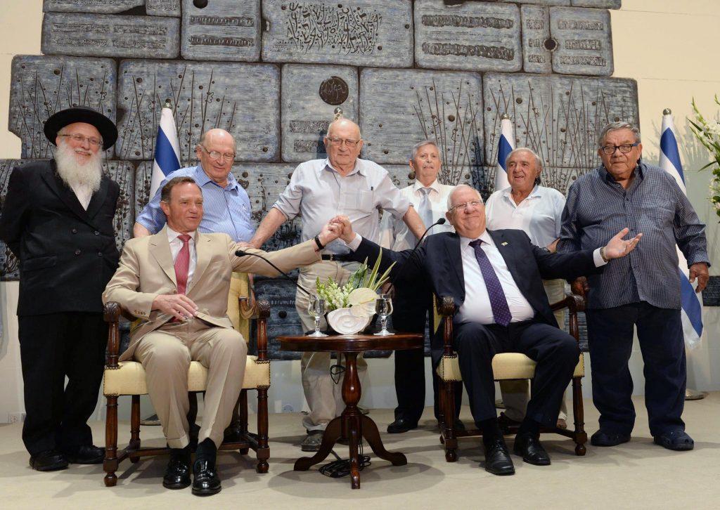 Israeli President Reuven Rivlin holding up the hand of Prince Michel De Ligne (seated Left), with (Left to Right, standing): Avraham Kaputka, Izhak Yerushalmi, Avraham Bromberg, Avraham Savignon, Albert Rasimora, and Efraim Elkuchen. (Mark Neiman/GPO)