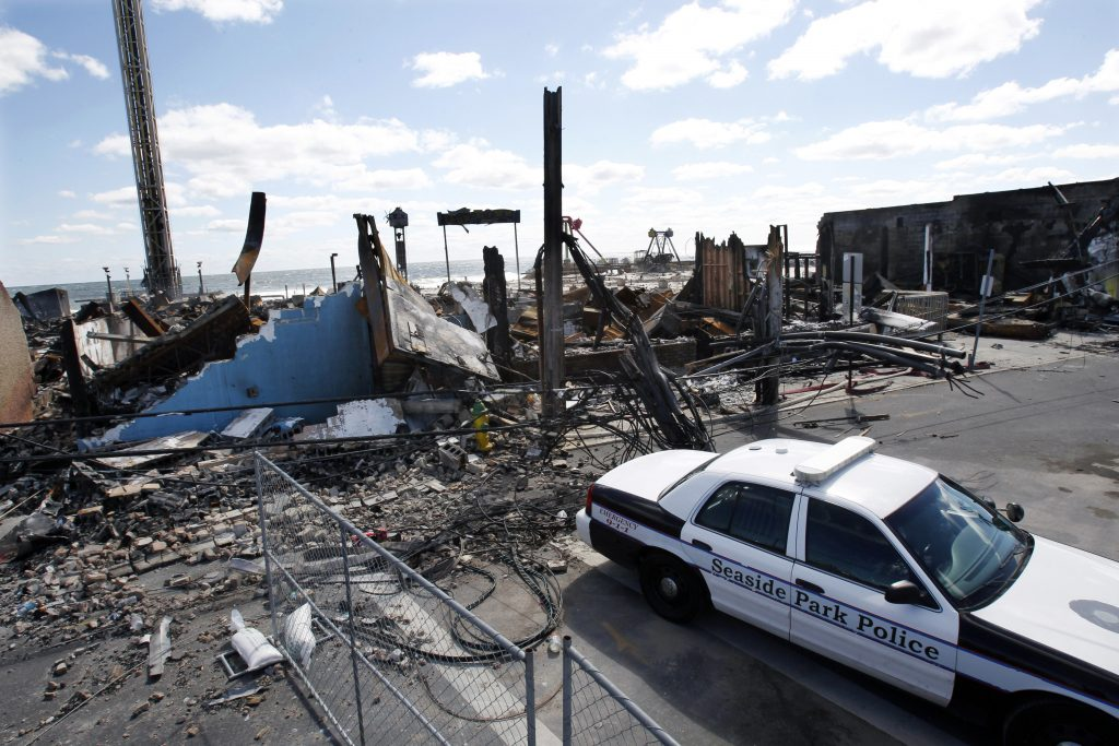 A police officer sits in his cruiser Sept. 17, 2013, along the boardwalk in Seaside Park, N.J., after a fire burned a historic Jersey shore pier that was pummeled by Superstorm Sandy. (AP Photo/Mel Evans, File)