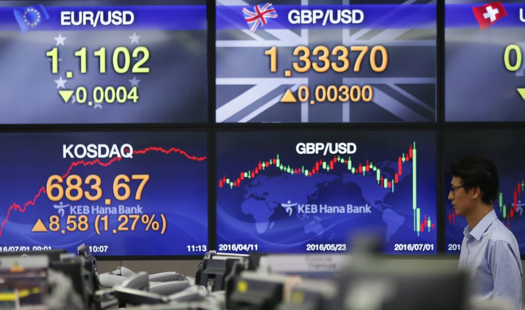 A currency trader stands near a screen showing the foreign exchange rates between the Pound and the South Korean Won currencies, center top, at the foreign exchange dealing room in Seoul, South Korea, Friday, July 1, 2016. Asian shares mostly rose Friday with investors remaining in a buying mood amid low interest rates and after world markets recovered their losses from Britain's vote to leave the European Union a week ago. (AP Photo/Lee Jin-man)