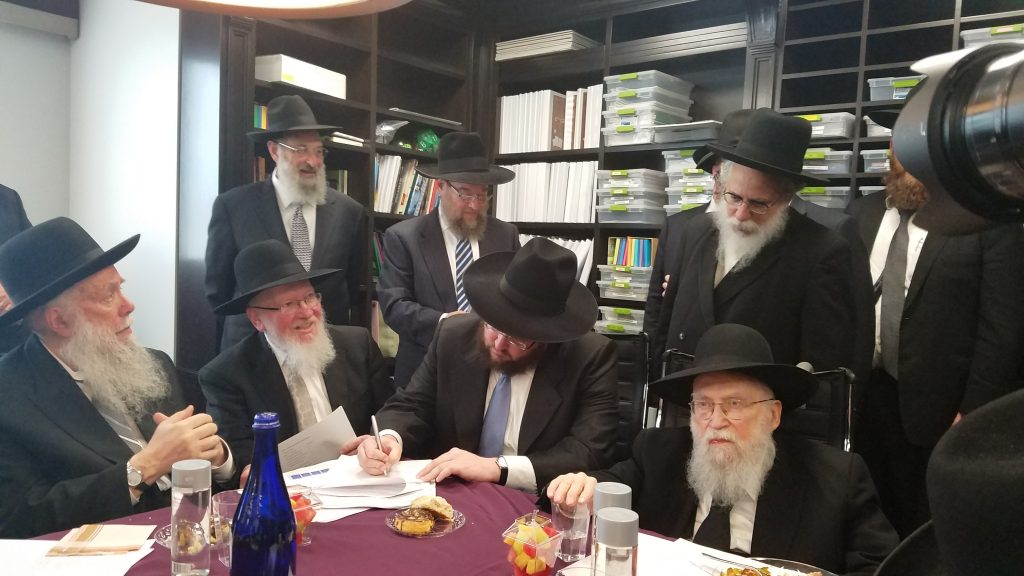 Reb Shia Piller signs a contract with Torah Umesorah last Tuesday at the Teachers Center of Lakewood on behalf of Talmud Torah Bais Avrohom. Standing behind him is Rabbi Avrohom Wulliger, the menahel of Bais Avrohom. Seated are (R-L) Harav Avrohom Chaim Levin, Rabbi Piller, Rabbi Dovid Nojowitz and Harav Hillel David.