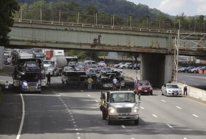 A construction truck moves past motorists stopped in the southbound lanes of Interstate 87 about a mile from the site of the crane collapse on the Tappan Zee Bridge, in Nyack, N.Y. (AP Photo/Julie Jacobson)