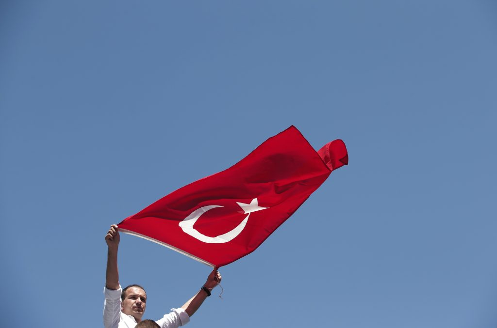A pro-government supporter waves a Turkish flag during a protest against the attempted coup, in Istanbul on Tuesday. (AP Photo/Lefteris Pitarakis)