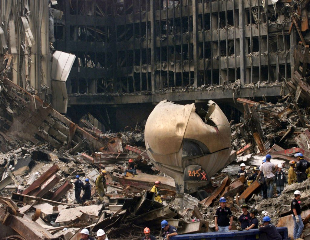 """In this Sept. 24, 2001, photo, Fritz Koenig's """"The Sphere"""" outdoor sculpture that once graced the plaza at New York's World Trade Center lies in the ruins of the 9/11 attacks. (AP Photo/Ted Warren, Pool/File)"""