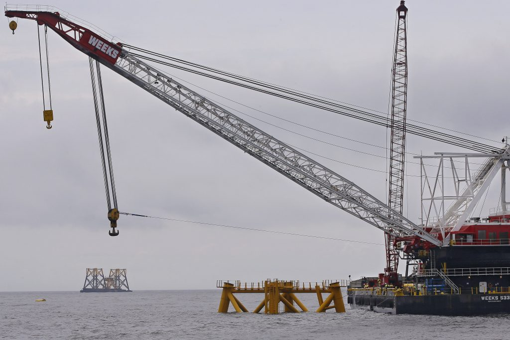 FILE - In this July 27, 2015 file photo, a construction crane works over a foundation for a wind turbine installed by Deepwater Wind in the nation's first offshore wind farm construction project off Block Island, R.I. Now another offshore site is under proposal, this time about 11 miles south of Long Island, N.Y. (AP Photo/Stephan Savoia, File)