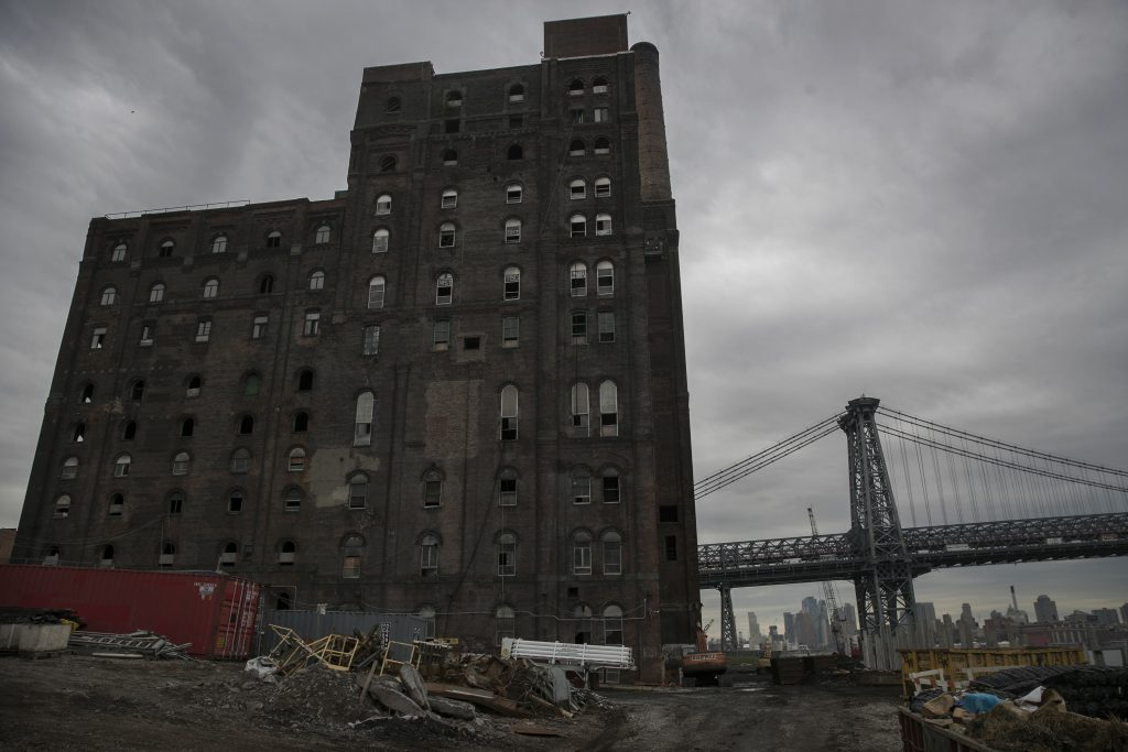 The former Domino Sugar Factory refinery building stands under construction in front of the Williamsburg Bridge in Brooklyn. (Bloomberg photo/Victor J. Blue)