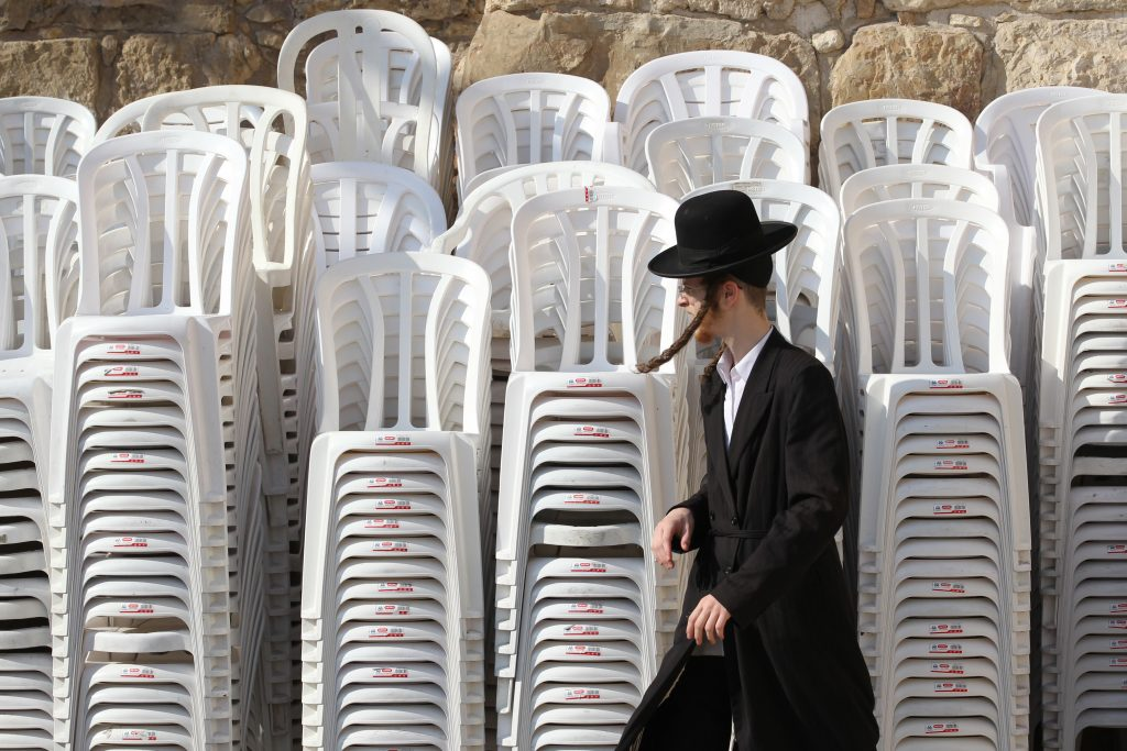 A Jewish ultra orthodox man walks by chairs piled up at the Western Wall in Jeusalem's Old City. September 27, 2011. Photo by Nati Shohat/Flash90. *** Local Caption *** ëñà çøãé çøãéí ëåúì