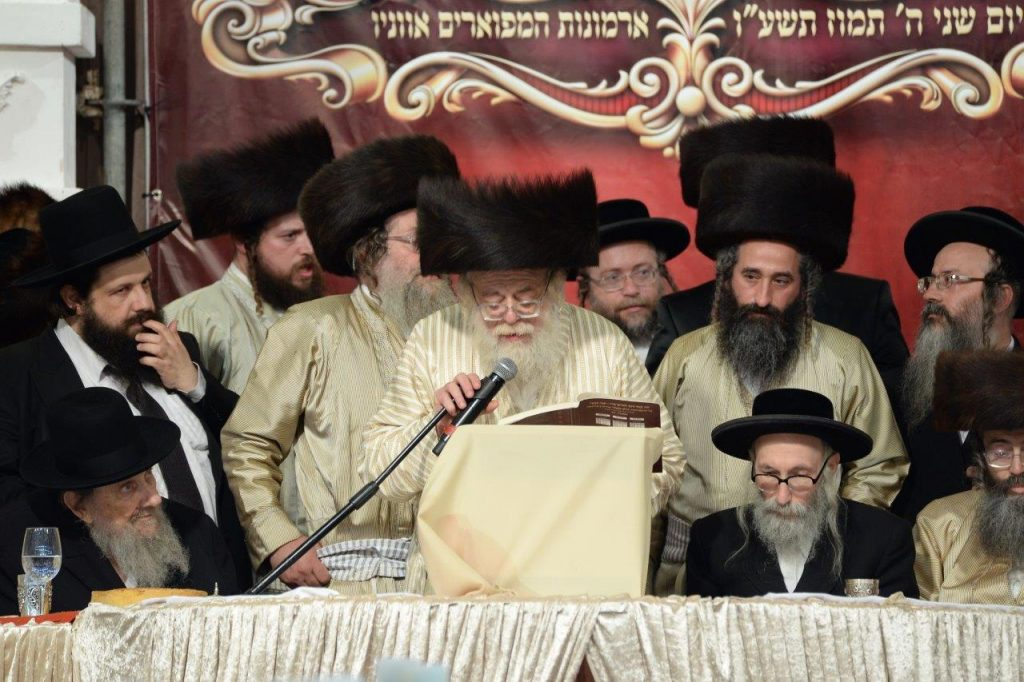 The Toldos Aharon Rebbe, shlita, completes the Shas at the siyum. (JDN)