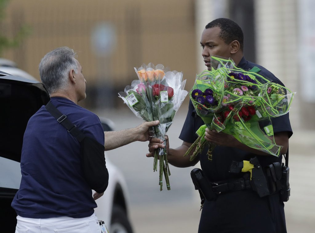 A Dallas police officer receivers flowers at a roadblock outside police headquarters on Saturday. (AP Photo/Eric Gay)