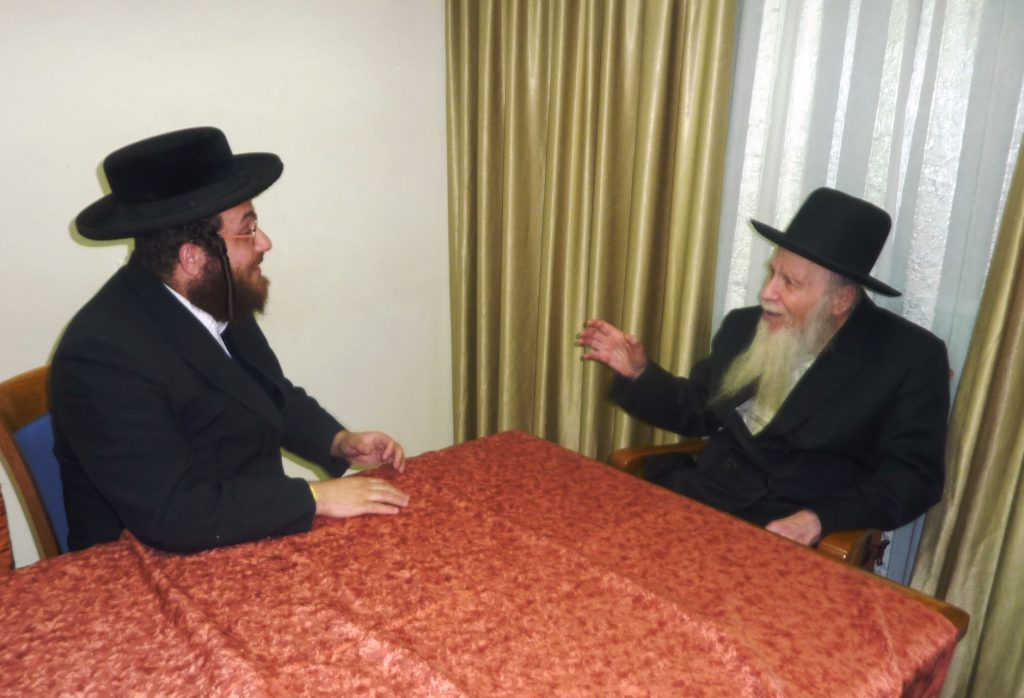 Harav Finkel (R) talks to Hamodia's Rabbi Tuvia Freund.