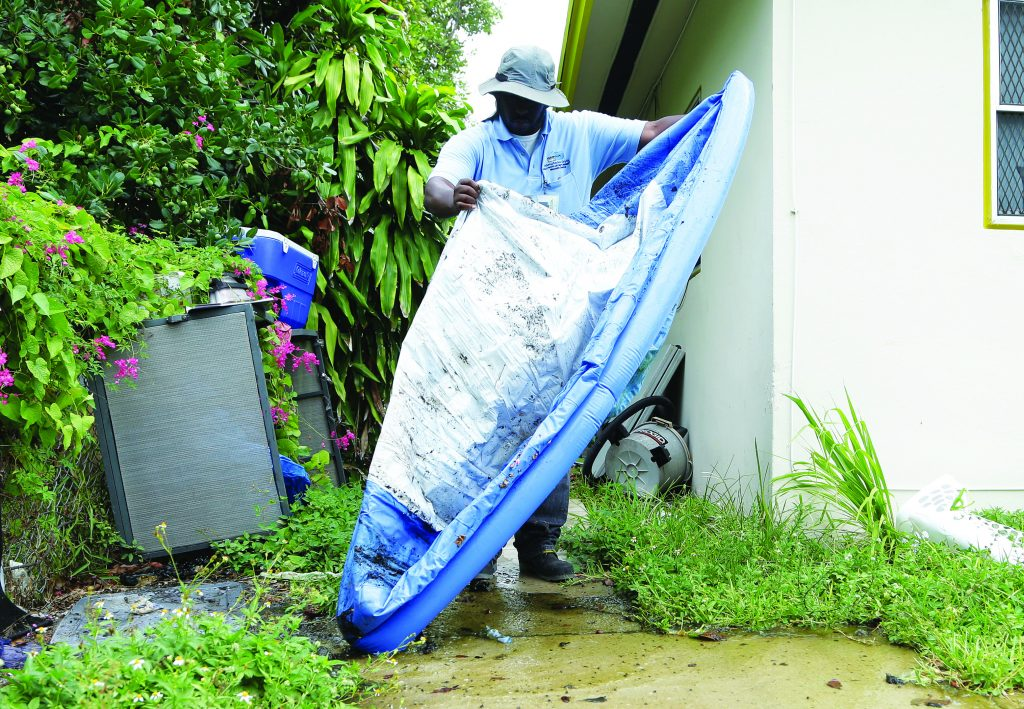 Joe Blackman, an inspector with the Miami-Dade County Mosquito Control Department, empties standing water from a swimming pool, Tuesday, in the Wynwood neighborhood of Miami.  (AP Photo/Lynne Sladky)