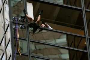 The climber tumbling into the open window after being pulled in by police. (Reuters/Lucas Jackson)