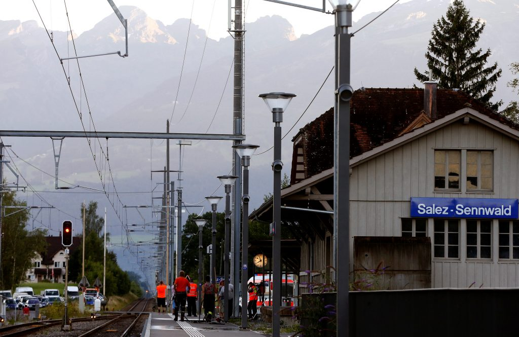 Workers clean a platform after the attack on a Swiss train at the railway station in the town of Salez, on Saturday.(Reuters/Arnd Wiegmann)