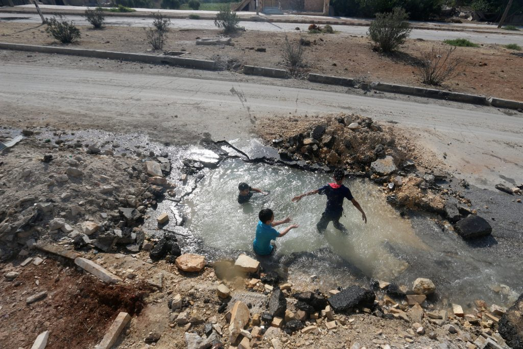 Boys cool down with water from a damaged water pipe due to shelling in the rebel-held Aleppo neighborhood of Sheikh Saeed on Saturday. (Reuters/Abdalrhman Ismail)
