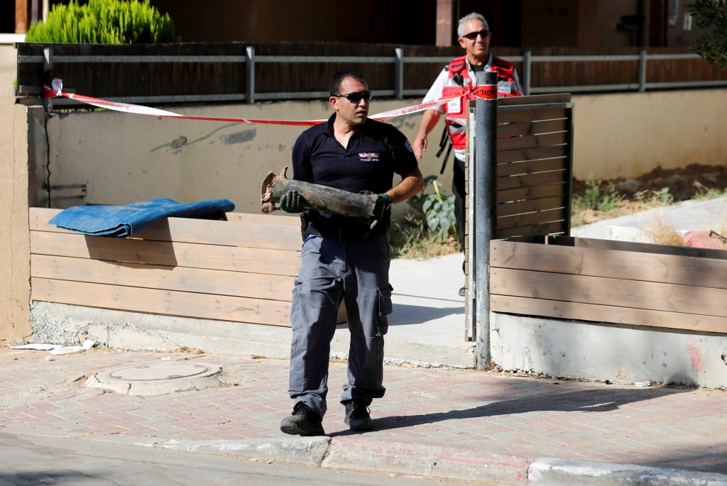 An Israeli policeman carries part of a rocket which the Israeli army and police said was launched from Gaza, landing next to a residential building in the Israeli southern town of Sderot, Israel August 21, 2016. REUTERS/Amir Cohen