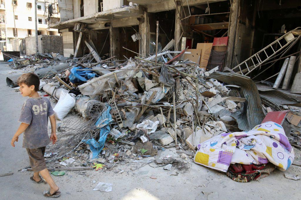 A boy walks past damaged shops in the rebel-held Tariq al-Bab neighborhood of Aleppo, on Monday. (Reuters/Abdalrhman Ismail)