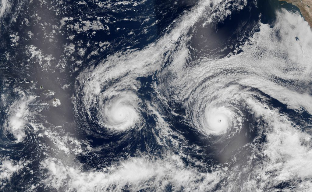 This satellite image taken Monday shows Hurricane Madeline, left, and Hurricane Lester over the Pacific Ocean, in a composite built from two overpasses by the Visible Infrared Imaging Radiometer Suite on the Suomi NPP satellite. (NASA via AP)