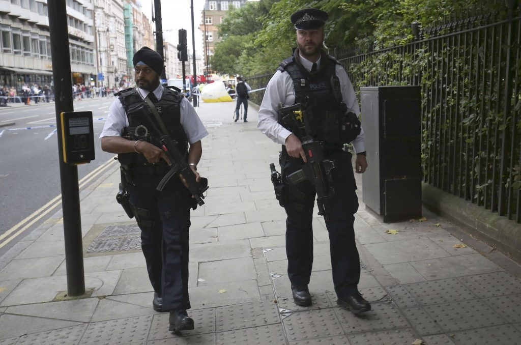 Armed police officers patrol past the scene of a knife attack in Russell Square in London, Britain August 4, 2016. REUTERS/Neil Hall