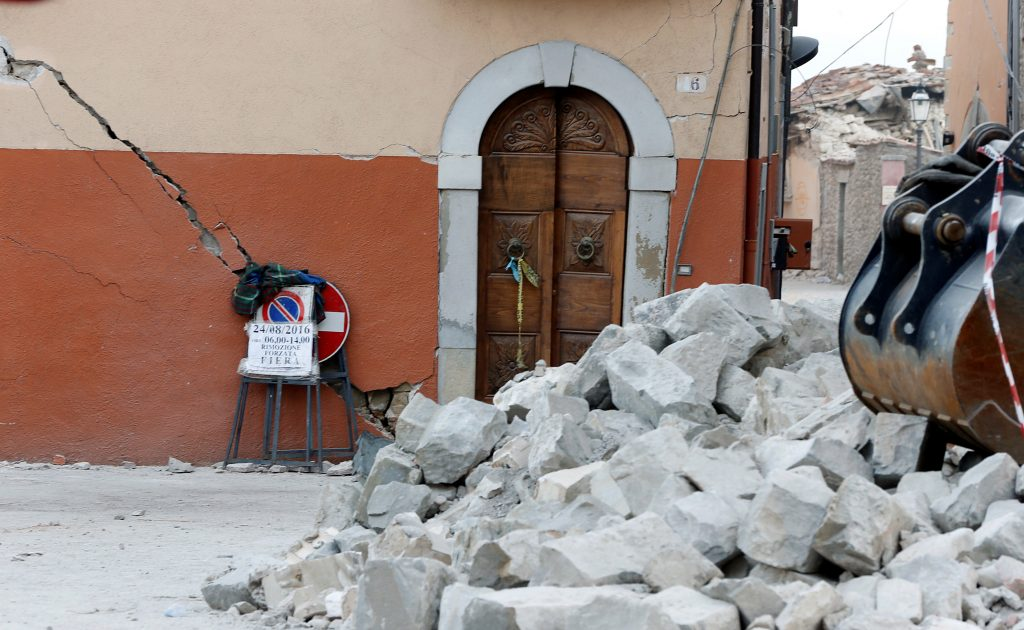 The door of a damaged house is seen behind rubble following an earthquake in Amatrice, central Italy, August 26, 2016. REUTERS/Ciro De Luca