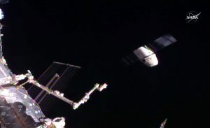 In this frame grab taken from NASA Television, a SpaceX Dragon capsule, right, separates from a robotic arm of the International Space Station en route back to Earth with a load of science experiments and gear from the space station on Friday. (NASA via AP)