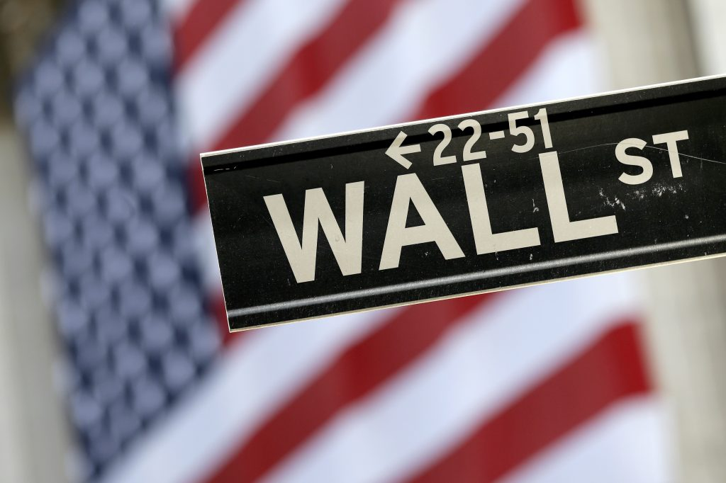 FILE - A Wall Street street sign is framed by an American flag hanging on the facade of the New York Stock Exchange. (AP Photo/Mary Altaffer, File)