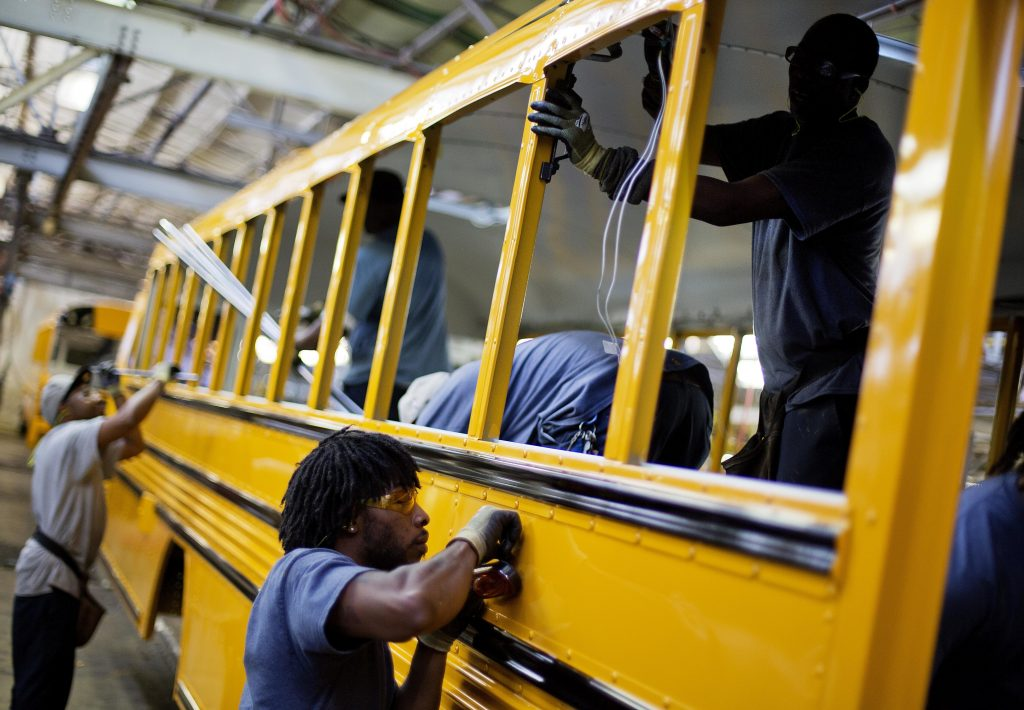 FILE - In this Friday, Sept. 18, 2015, file photo, employees work on a school bus on the assembly line at Blue Bird Corporation's manufacturing facility, in Fort Valley, Ga. On Tuesday, Aug. 9, 2016, the Labor Department releases second-quarter productivity data. (AP Photo/David Goldman, File)