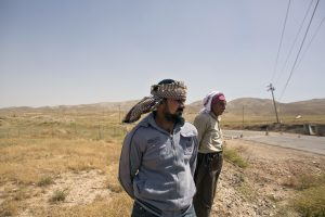 Arkan Qassim, center, stands at the site where he witnessed the killing dozens of Yazidi men, including two sons of Rasho Qassim, right, in August 2014, in Hardan, northern Iraq. (AP Photo/Maya Alleruzzo