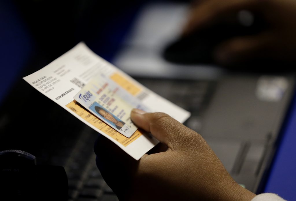 FILE - In this Feb. 26, 2014, file photo, an election official checks a voter's photo identification at an early voting polling site in Austin, Texas. (AP Photo/Eric Gay, File)
